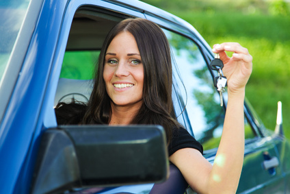 Young and beautiful lady holding car keys and posing from her blue car